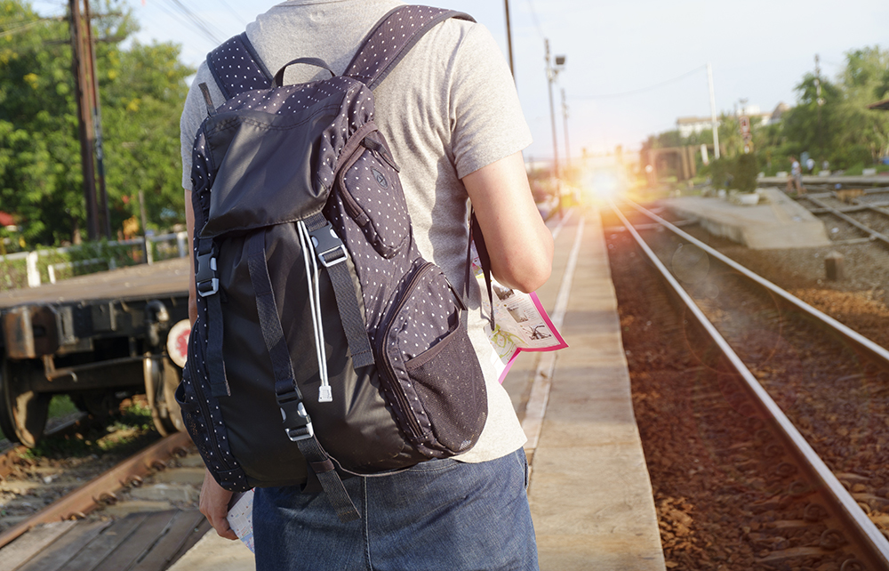 young man traveler with backpack  at the train station with a traveler , travel and recreation concept